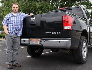 Photo of a man standing next to a black pickup truck.