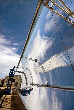 Photo of a woman on a lift silhouetted against the sky and reflected in the solar collector.