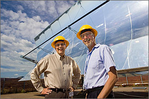 Photo of two men in yellow hard hats standing and smiling in front of an enormous reflective, curved piece of metal.