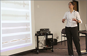 Photo of a woman in front of a screen pointing giving a talk.