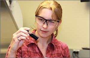 Photo of  a woman eyeing a test tube of black liquid.