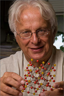 Photo of a man holding a model of an atomic structure made of red and yellow beads connected by wires.
