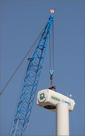 Photo of a large crane maneuvering a large white metal gearbox to the top of a wind turbine tower.