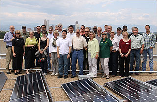 Photo of a group of people standing on a roof in front of solar panels.