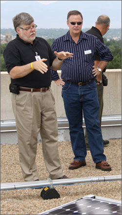 Photo of two men talking on a roof.