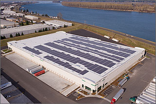 Aerial photo of a warehouse with a white roof and many rows of solar panels.