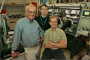 Photo of three men in a laboratory. In the background is a glovebox.