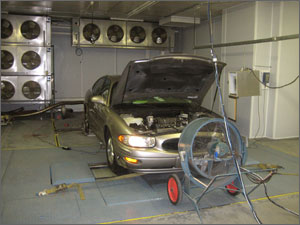 Photo of a car with the hood up, lights on, running on rollers in a testing facility.