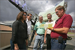 Photo of four men and a woman examining a piece of yellowed glass with a device made of mirrors in the background.