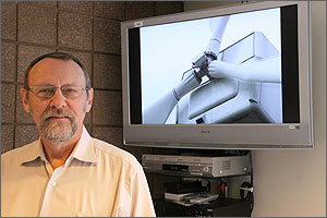 Photo of bearded man wearing glasses and standing next to a TV screen showing a close up of a wind turbine.