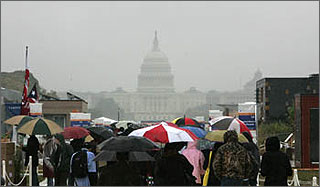 Photo of people holding umbrellas touring rows of solar-powered homes in the rain with the dome of the U.S. Capitol visible in the foggy background.