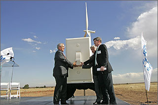 Photo of a three men standing in front of a giant light switch with a wind turbine in the background.