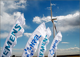 Photo of white flags that say Siemens and NREL flutter in front of a giant wind turbine.