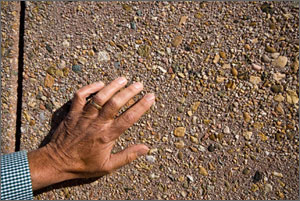 Photo of a man's hand against a wall embedded with small stones.