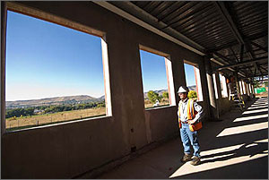 Photo of a man standing inside of a building under construction looking at unfinished walls and windows.