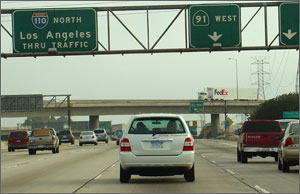 Photo of a white SUV driving on the highway with overhead signs directing Los Angeles traffic.