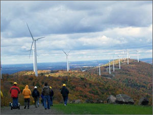 Photo of white wind turbines lining the crest of a hill extending into the horizon. Several people dressed in cold weather clothing walk towards the turbines under cloudy skies.