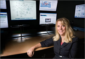 Photo of a woman sitting in front of an array of flat screens displaying energy information.