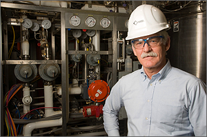 Photo of a man in hard-hat standing next to equipment in a biofuels conversion facility.