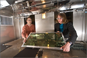 Photo of a man and a woman wearing safety glasses and leaning through hatchways into a scientific chamber. They are positioning a rectangular window inside the chamber for simulated weather testing.