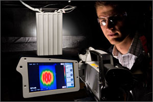 Photo of a Test engineer standing next to a camera showing a thermal image of a battery being tested.