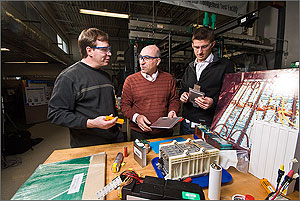 Photo of three men standing in front of various battery components in a laboratory.