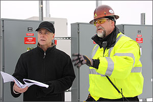 Photo of two workmen dressed warmly while working outside on a winter day. The man on left is dressed in a black parka and black ball cap and he is holding construction plans printed on wide sheets of white paper. The man on the right is dressed in a bright yellow safety parka and he is wearing safety glasses and a red hard hat.