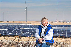 Photo of a woman with a field of photovoltaic panels and a wind turbine in the background.