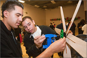 Photo of Denver West High School juniors Luis Solis and Jose Santistevan checking the blades on their wind turbine.  The balsa-wood turbines are glued to small dowels.