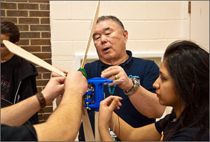 Photo of NREL education consultant Rick Shin helping Nicole Nuxoll from Denver West High School with her wind turbine. The turbine has three balsa-wood blades about a foot long. A plastic box is attached so the volts generated when the turbine is blasted by a fan can be measured.