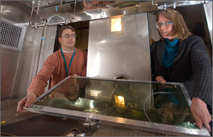 Photo of a man and a woman in a lab holding a window with tinted glass.