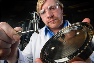 Photo of a scientist using highly specialized tweezers to place a tiny sample of biomass on a round metal plate so it can be analyzed by NREL's new high throughput pipeline.
