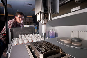 Photo of a scientist peering at a robot dropping enzymes into a tiny cup of poplar sawdust