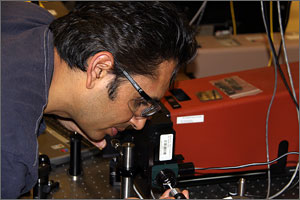 Photo of a man carefully putting a sample into a machine.