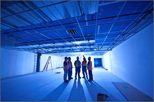 Photo of five people in construction vests and hard hats gazing toward the ceiling of the data center in NREL's Research Support Facility.