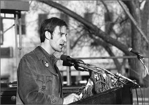 Photo of Earth Day organizer Denis Hayes, in worn leather jacket, addressing an Earth Day crowd from a podium ornamented with evergreen branches.