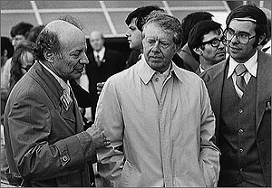Photo of  US President Jimmy Carter on his visit to SERI in 1979. Accompanying him are SERI's first director, Paul Rappaport, and solar scientist Larry Kazmeski. Carter is wearing a light-colored overcoat in the black-and-white photo.