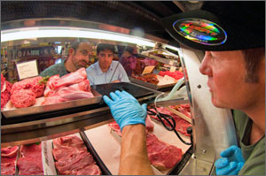 Photo of a meat counter at a Whole Foods Market. The image is taken from the inside of the meat counter looking out into the store at NREL researchers Michael Deru and Ian Doebber. Also pictured is Dale Moore, Meat Team Leader at Whole Foods.