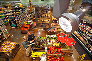Photo of the interior of a Whole Foods Market. The image is an aerial shot of the produce section. In the top right corner of the image is a close-up view of one of the light fixtures used in this area. In the photo are Michael Deru, a researcher at NREL, and Kyle Maier, a Whole Foods Market Produce Team Leader.