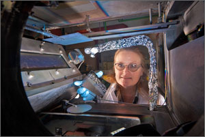 Photo of a scientist wearing safety glasses and loading a small mirror into an enclosed high intensity light chamber for testing.