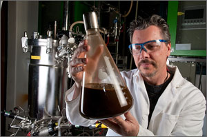 Photo of a scientist holding a flask of brown liquid used in making biofuels from plants