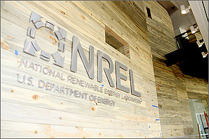 Photo of a building lobby with the NREL logo on top of wood planks with colors of gold and blue-gray.