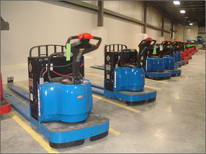 Photo of a line of blue and red forklifts ready for use in a warehouse.
