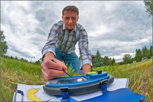 Photo of a man in a checkered shirt kneeling in a field on a cloudy day using a stylus to check a SunEye device the size of a laptop.