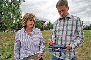 In this photo, a man in a checkered shirt uses a stylus to check data on the SunEye device, while a woman holding a clipboard looks on.