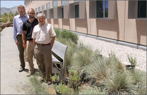 Photo of three men standing outside a building surrounded by prairie grasses.