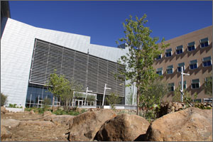 Photo of the outside of a building with large boulders and trees in the foreground and bright blue sky above.