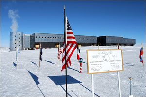 Photo of a modular building atop a snowfield with the U.S. flag and the flags of other nations in the foreground.