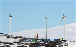 Photo of three wind turbines operating on a barren hillside with a snow-covered mountain rising in the background.