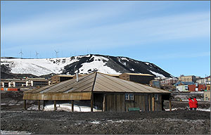 Photo of dormitories and other prefabricated modular building on bare ground at the McMurdo Research Station in Antarctica. Three wind turbines are visible on the crest of a hill behind the buildings.